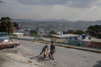 Unos jóvenes cargan botellones de agua en La Pastora, en Caracas