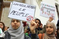 """Women hold posters reading """"Only one hero, the people,"""" left, and """"The power belongs to the people"""" during a demonstration in Algeria on March 8. (Anis Belghoul/AP)"""