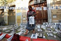 Indigenous activist Rosalina Tuyuc leaves photographs of victims of Guatemala's civil war outside the Congress in Guatemala City on March 13. (Esteban Biba/ EPA-EFE)