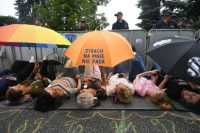 Protesters hold umbrellas while lying on the ground next to a barrier guarded by police men during a demonstration in front of the Sejm building in Warsaw, Poland, on July 20, 2017. (Bartlomiej Zborowski/EPA)