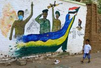 A Sudanese child walks past a mural depicting protesters and soldiers on a street in Khartoum, Sudan, on Tuesday. Sudanese protesters continued their sit-in and gatherings near the army headquarters, pressing for a civilian council instead of the current military one. (Str/EPA-EFE/REX/Shutterstock)