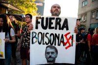 Frente al Palacio de La Moneda, la sede del ejecutivo de Chile, un hombre despliega un cartel contra Jair Bolsonaro. Credit Martín Bernetti/Agence France-Presse — Getty Images