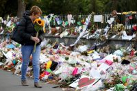 A woman walks past flowers and tributes displayed in memory of those who died in a mass shooting in Christchurch, New Zealand, last month. (Sanka Vidanagama/AFP)