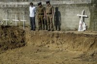 Police officers survey graves prepared for the victims of the Easter Sunday attacks in Sri Lanka. (Atul Loke/Getty Images)