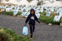 A Yemeni child holding empty bottles walks past portraits on the graves of Yemenis killed in the country's ongoing conflict at a cemetery in Sanaa, Yemen, on April 17. (Yahya Arhab/EPA-EFE/REX)