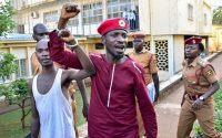 Opposition leader Bobi Wine walks handcuffed together with another prisoner before boarding a bus to prison in Kampala, Uganda, on April 29. (Nicholas Bamulanzeki/AFP/Getty Images)