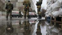 Pro-Russian separatists patrol the street in front of Russian humanitarian trucks in Makiivka (Makeyevka) in Donetsk region, 12 December 2014. REUTERS/Maxim Shemetov