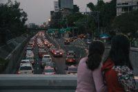 Dos mujeres pasan por un puente que ve hacia el viaducto Miguel Alemán, en Ciudad de México, durante la hora pico. Credit Luis Antonio Rojas para The New York Times