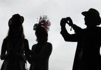 Un hombre toma una foto de dos mujeres, en una carrera de caballos en Kentucky, el pasado 3 de mayo. Charlie Riedel AP