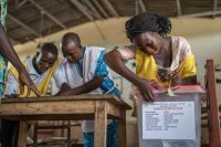 A polling official cuts the seal of a ballot box during the elections for a new parliament in Cotonou, Benin, on April 28. (Yanick Folly/AFP/Getty Images)