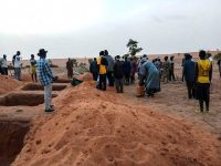 Officials and residents stand near freshly dug graves in the Dogon village of Sobane-Kou on Tuesday after an attack that killed over 100 ethnic Dogon. (Stringer/AFP/Getty Images)