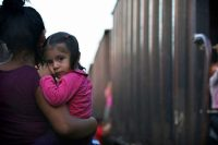 A migrant mother and child wait for a northbound freight train in Salto del Agua, Chiapas state, Mexico, on June 24. (Marco Ugarte/AP)
