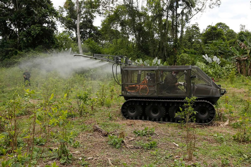 A counter-narcotics police officer testing a tactical vehicle to spray herbicides on a coca field in Tumaco, southern Colombia, in 2018. (Fernando Vergara/AP)