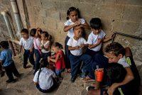 Un grupo de niños espera comer en un comedor de beneficencia en Caracas en febrero de 2019. Credit Meridith Kohut para The New York Times