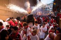 """A man wearing a costume of """"Toro de Fuego"""" (bull of fire) chases people during the San Fermin Festival on Tuesday in Pamplona, Spain. (Jaime Reina/AFP/Getty Images)"""