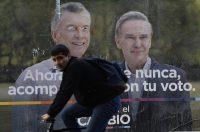 Un hombre en bicicleta pasa frente a un anuncio de la fórmula a la presidencia de Juntos por el Cambio.CreditCreditJuan Mabromata/Agence France-Presse — Getty Images