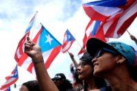 Algunos manifestantes ondean banderas de Puerto Rico en la protesta masiva en San Juan el 25 de julio de 2019. Credit Ricardo Arduengo/Agence France-Presse — Getty Images