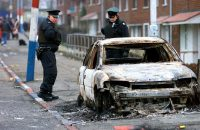 Police Service of Northern Ireland officers look at a burnt car in the Ardoyne area of north Belfast in 2002, after Catholic and Protestant rioters clashed with police overnight. (Peter Morrison/AP)