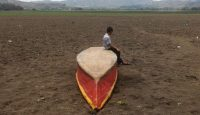 A boy sits on an abandoned boat on what is left of Lake Atescatempa, which has dried up due to drought and high temperatures, in Atescatempa, Guatemala on 5 May 2017.