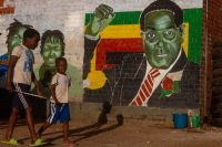Children pass in front of a wall with a mural of the Robert Mugabe in Harare, Zimbabwe, on Saturday, a day after his death. (Tafadzwa Ufumeli/Getty Images)