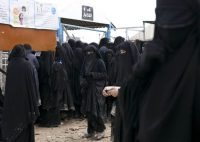 Women line up for aid supplies at al-Hol camp in Hassakeh province, Syria, on March 31. (Maya Alleruzzo/AP)