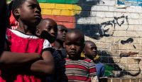 Children stand beside a mural of former Zimbabwe president Robert Mugabe in Harare. Photo: Getty Images.