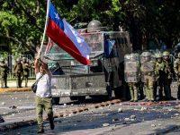 Un protestante sostiene una bandera chilena frente a un vehículo policial durante las protestas en Santiago el 28 de octubre de 2019. (MARTIN BERNETTI/AFP vía Getty Images)
