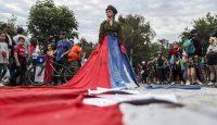 Una mujer, vestida de militar y envuelta en la bandera de Chile, en las protestas del pasado domingo 27 de octubre en Santiago. Esteban Felix AP