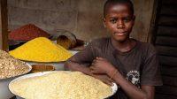 Un niño junto a una bandeja de arroz en su tienda en el mercado de Ajara en Badagry, cerca de Lagos, en Nigeria. Benson IBEABUCHI (AFP)