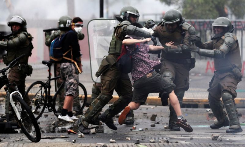 Protesters and police clash in Santiago on 23 October. Photograph: Iván Alvarado/Reuters