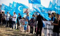 Demonstrators holding Uighur flags demonstrate next to the Chancellery in Berlin. Photograph: Kay Nietfeld/AFP/Getty Images