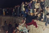 On Nov. 10, 1989, East Berliners get help from West Berliners as they climb the Berlin Wall near the Brandenburg Gate. (Jockel Finck/AP)