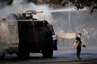 A demonstrator plays a drum as police use a water cannon during an anti-government protest in Santiago on Oct. 30. (Edgard Garrido/Reuters)