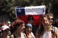 Una persona alza la bandera chilena en una manifestación contra el modelo económico del país en octubre de 2019.Credit...Henry Romero/Reuters