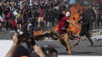 Un joven lanza piedras contra la policía durante una protesta en Santiago de Chile. AFP