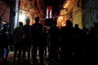 Un grupo de personas se reúne bajo una bandera cubana durante las celebraciones del aniversario de los Comités de Defensa de la Revolución (CDR) en La Habana, en septiembre de 2019.Credit...CreditAlexandre Meneghini/Reuters