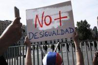 Una manifestante levanta una pancarta contra la desigualdad frente a La Moneda, el palacio presidencial en Santiago, la capital chilena.Credit...Rodrigo Abd/Associated Press