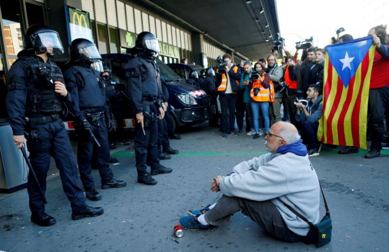 A man sits in front of riot police as pro-Catalan independence demonstrators protest Nov. 16 outside the Barcelona Sants railway station. (Enrique Calvo/Reuters)