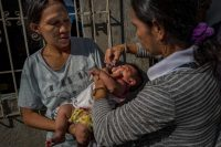 A community health worker administers an oral polio vaccine to a child, during a mass vaccination campaign in Manilla, Philippines, on Oct. 13. (Ezra Acayan/Getty Images)