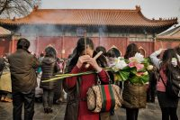 A woman offers joss sticks and prayers at the Lama Temple in central Beijing, a place of worship very popular with locals praying for wealth and good health.Credit...Sim Chi Yin/Magnum Photos