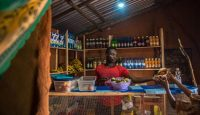 A man serves customers at a shop in Nyahbiheke Refugee Camp, Rwanda. Energy access makes it possible for refugees to power and run businesses. Photo: Practical Action.