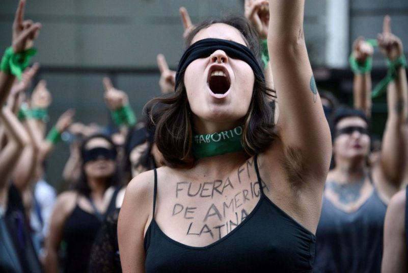 """Women participate in a demonstration against gender violence in Buenos Aires on Dec. 6. The writing on the woman's chest reads """"IMF, get out of Latin America."""" (Magali Druscovich/Reuters)"""