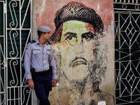 Un miembro de la Policía Nacional Revolucionaria de Cuba permanece de guardia frente a un mural del Che Guevara. Credit... Yamil Lage/Agence France-Presse — Getty Images