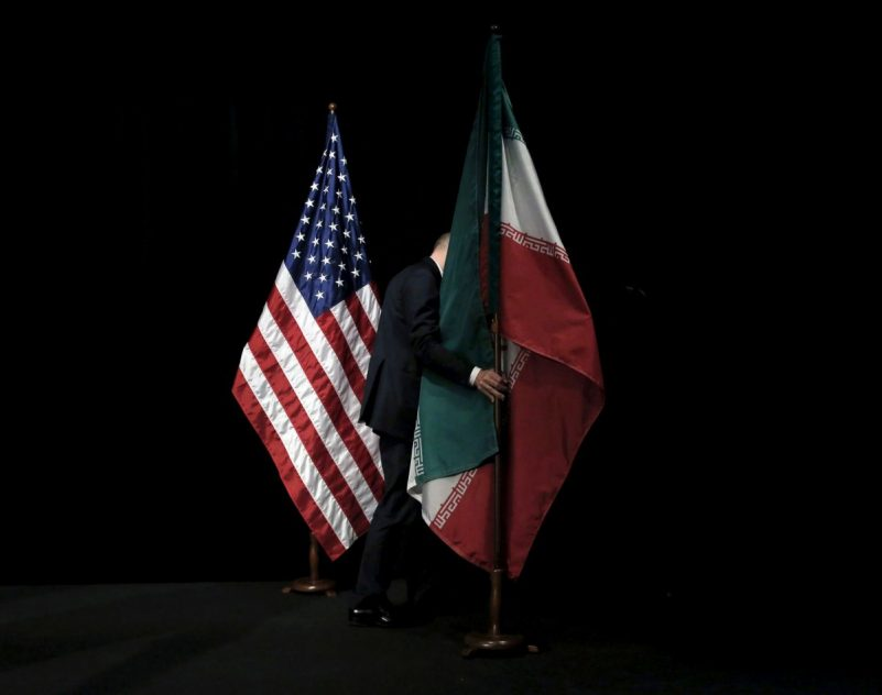 A United Nations staff member moving the flags of Iran and the United States after a group photo during the 2015 Iran Nuclear talks. Credit Carlos Barria/Reuters