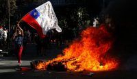 A demonstrator waves a Chilean flag during a protest in Santiago on 21 October 2019. Photo: Getty Images.