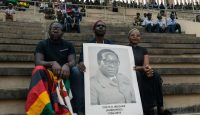 A man holds a portrait of Robert Mugabe during his official funeral ceremony. Photo: Getty Images.