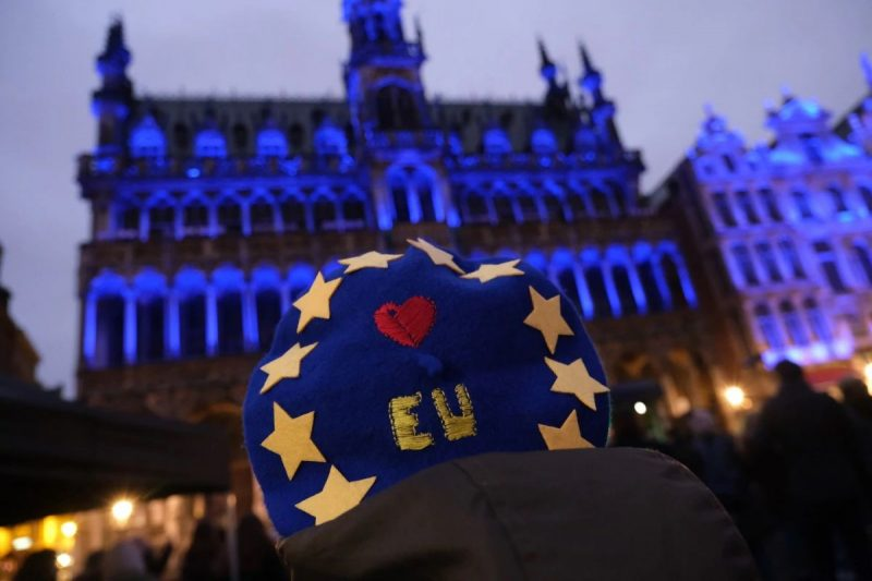 """A woman attends a concert in Brussels as buildings pulsate with lights in the red, blue and white of the British flag during a British-themed evening titled """"Brussels Calling"""" on Thursday. (Sean Gallup/AFP/Getty Images)"""