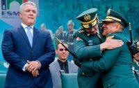Duque, de fondo, observa el abrazo del excomandante del ejército colombiano Nicacio Martínez (al centro) con su reemplazo, Eduardo Zapateiro (a la izquierda).Credit...Raúl Arboleda/Agence France-Presse — Getty Images