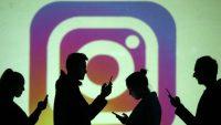 Usuarios de móviles, frente al logotipo de Instagram. Dado Ruvic (REUTERS)