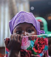Una niña somalí asiste a una clase en una escuela improvisada en el campamento de Badbaado para desplazados internos en Mogadiscio, Somalia. Desde 2017, estudiantes universitarios se han ofrecido como voluntarios para enseñar a unas 600 niñas y niños menores de 16 años en campamentos.Credit...Mohamed Abdiwahab/Agence France-Presse — Getty Images